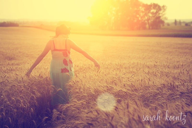 Woman walking on wheat field at summer sunset