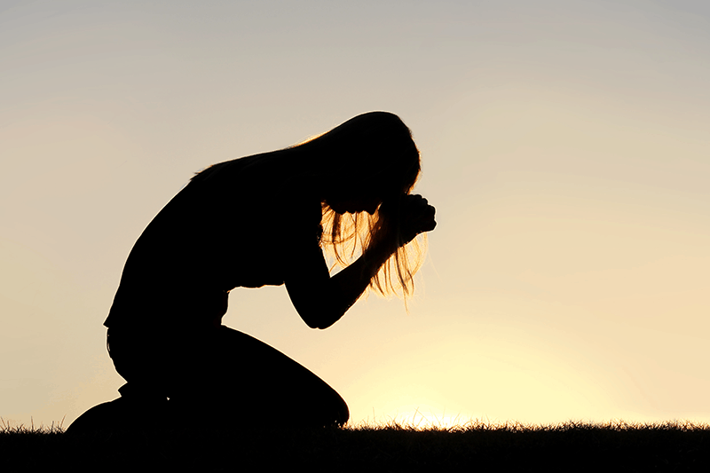 Silhouette of person on knees praying, depicting Jesus