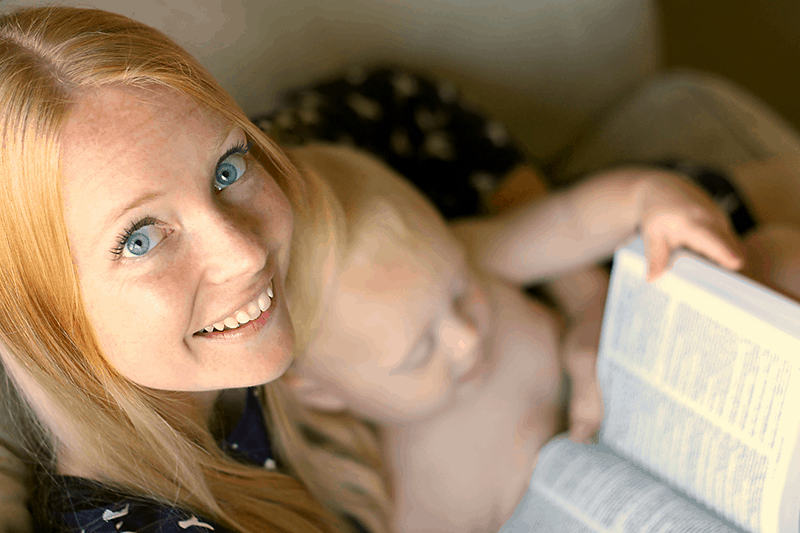Happy woman reading Bible with baby