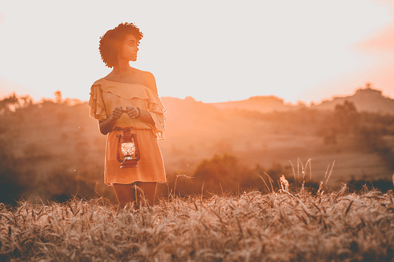 Woman at sunset in field holding lantern with calm expression and a desire to build enduring hope in God.