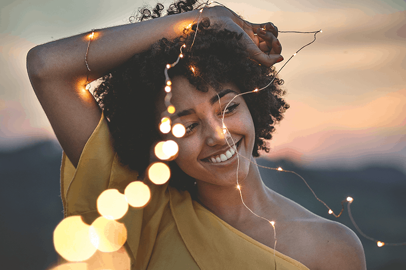 Beautiful ethnic woman with a hopeful expression on her face holding a string of lights at dusk