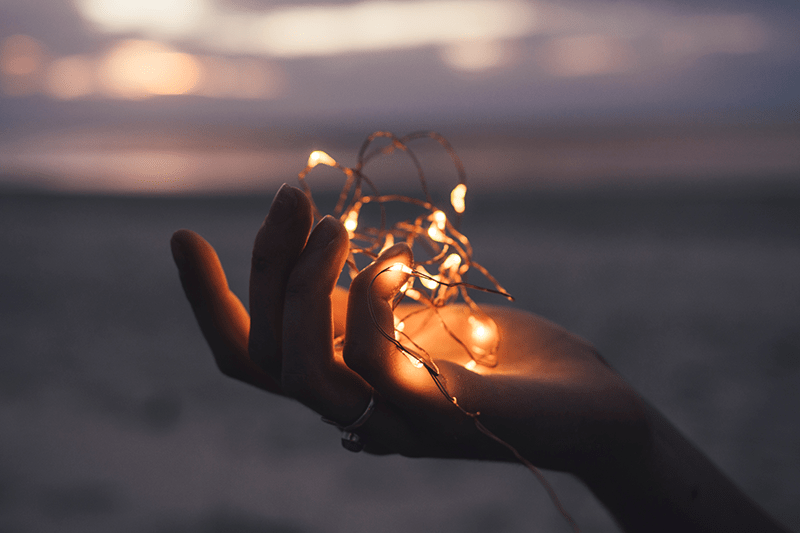 twinkle lights in woman's hand at sunset inspiring her to build enduring hope in God.