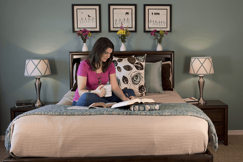 Christian woman on bed with coffee and Bible completing a yearly Bible reading plan