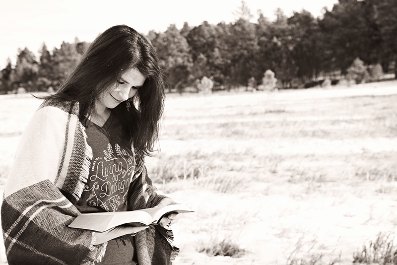 Woman outdoors reading Bible to complete her daily bible reading plan