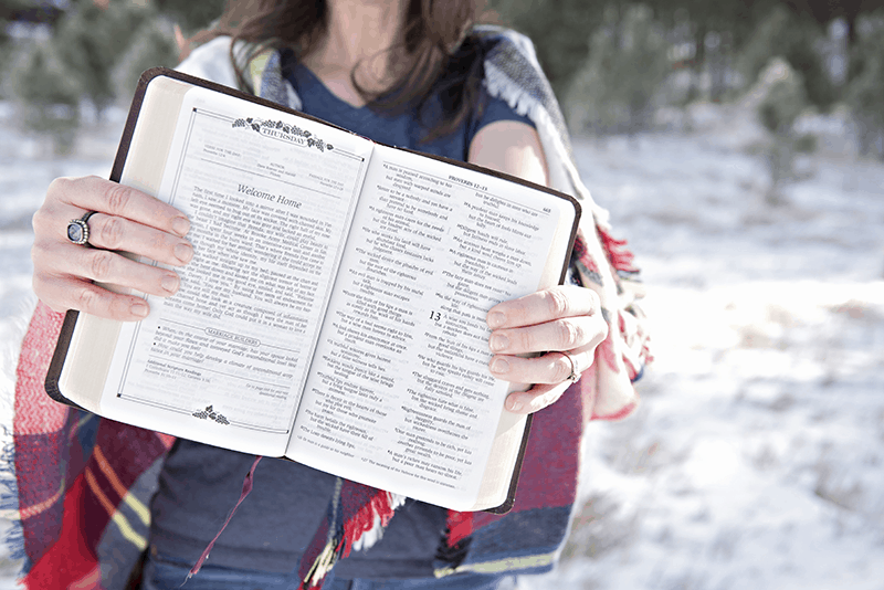 Christian woman holding a Bible outdoors with snowy background