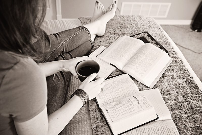 Christian woman with reference books and journal drinking coffee and doing her bible reading plan