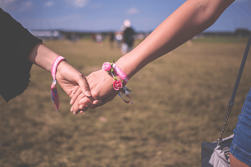 Two christian women holding hands as part of our online prayer community