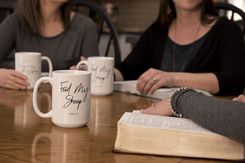 Christian Women from the Living by Design Support Team with coffee mugs and Bibles