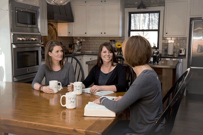 Three Christian Women seated at a table discussing God's Word and drinking coffee