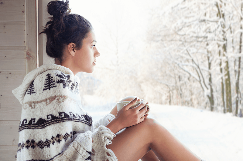 Brokenhearted woman looking out at a snowy landscape