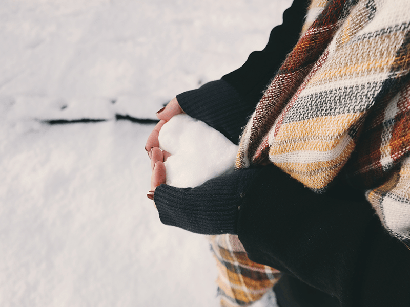 brokenhearted woman with a snowball shaped like a heart in her hands