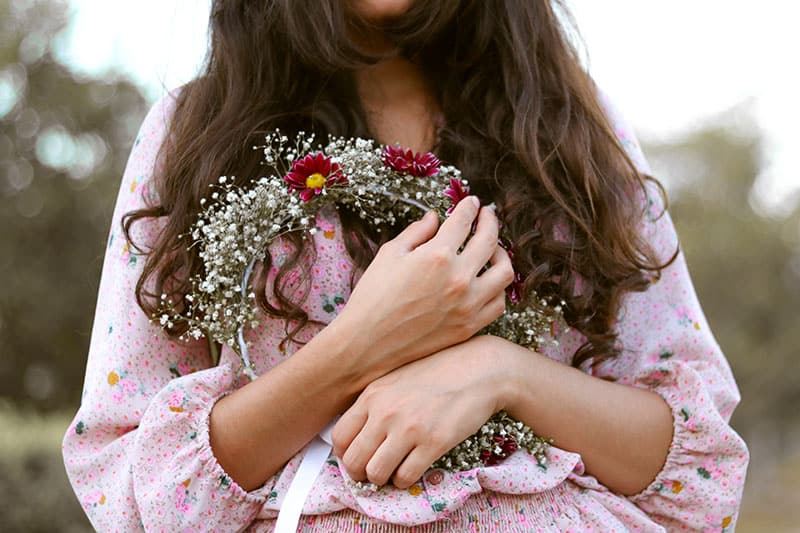 christian woman holding flower crown lifting small prayers to god