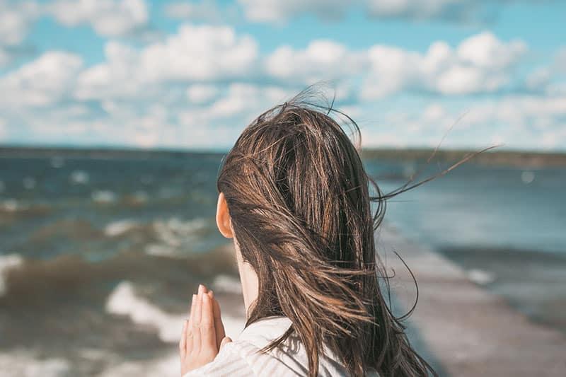 christian woman on the beach praying