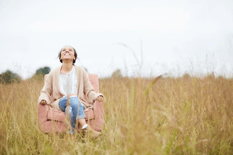 christian woman sitting in chair praising god for sabbath rest