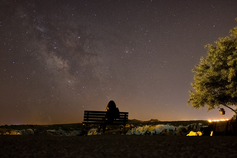 christian woman sitting on bench under the stars struggling with doubt