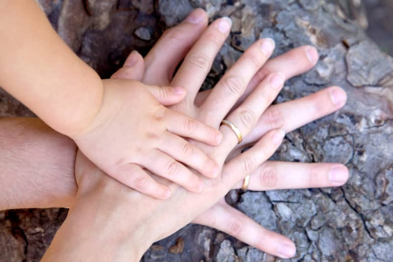 Family hands stacked together in unity on top of a tree trunk, standing against spiritual warfare together.