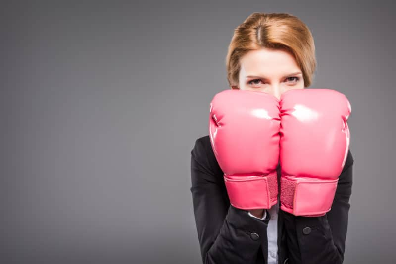 Woman with pink boxing gloves preparing for spiritual warfare.