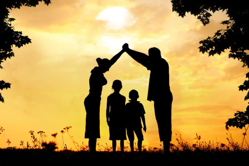 Silhouette of a family at sunset preparing for spiritual warfare battle.