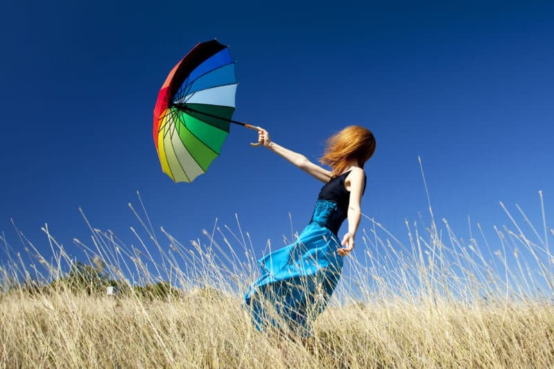 Woman in a windy field holding a colorful umbrella, thinking about how, like the wind, spiritual warfare is unseen.