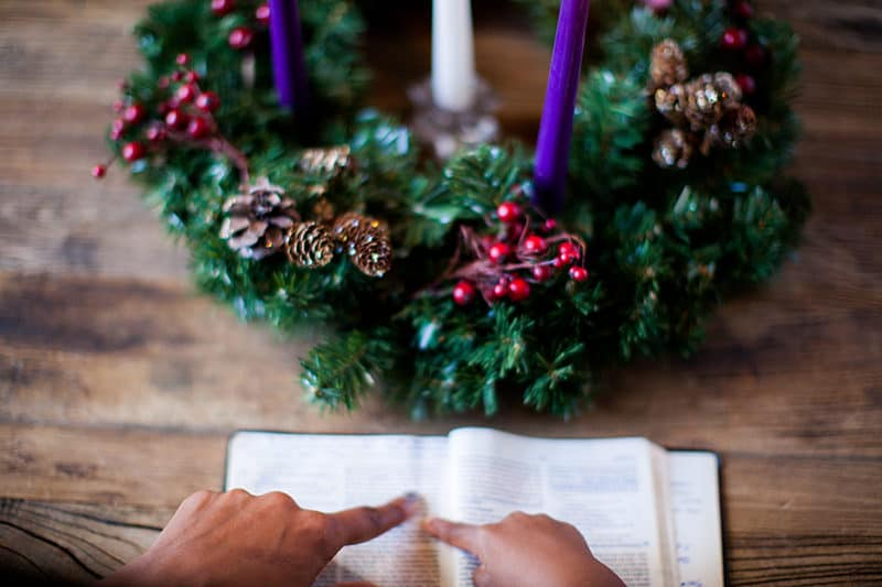 Christmas wreath with advent candles and woman reading scripture