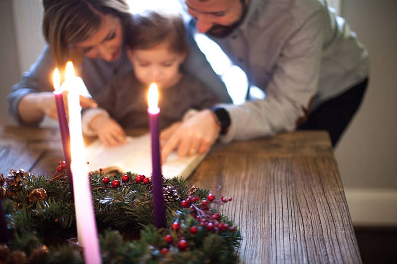 mother and father reading scripture with their child. Lighted advent wreath in the foreground.