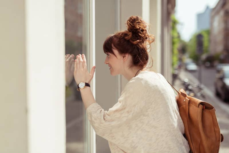 redhead woman looking through the glass of a storefront window | free word30 challenge