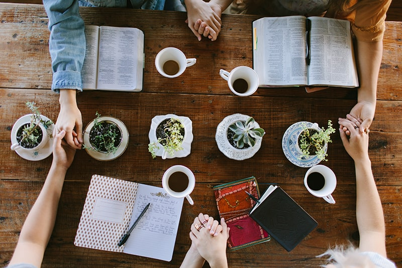 close up of women holding hands around a table as they study the Word together | Make Room for Jesus with our Word30 Challenge