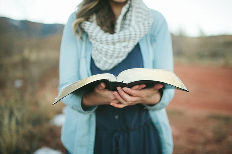 Christian Woman in a Field with Her Bible | 2018 Annual Report for Living by Design Ministries