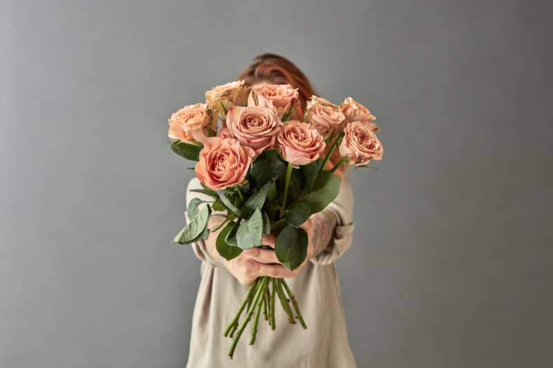 woman holding forward bouquet of roses: a post about Jesus calling us to love the lost