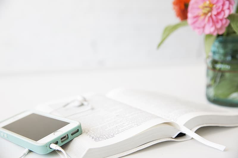 """Open Bible with cell phone beside 