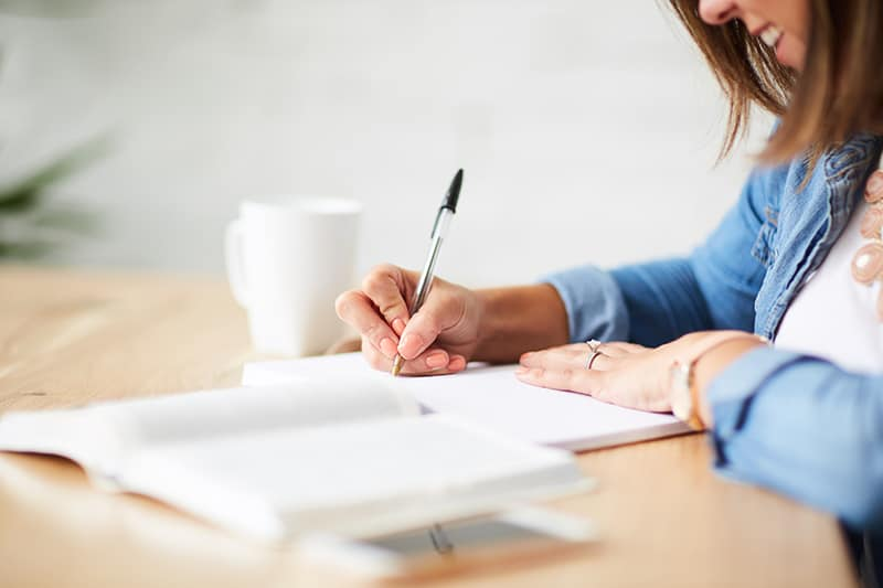 """woman sitting at a table doing a Bible study 