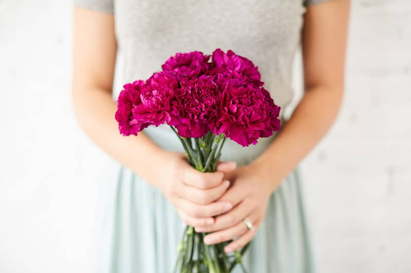 "Woman's hands holding carnations | Sign up today for our free online Bible study on God's divine rescue plan for His people, entitled ""RescYOUed"". 
