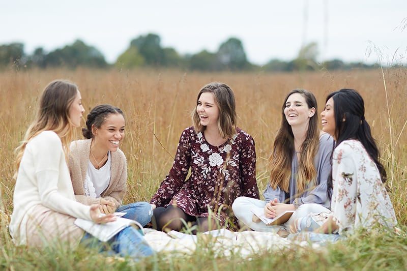 """Young women sitting in a field having a Bible study 