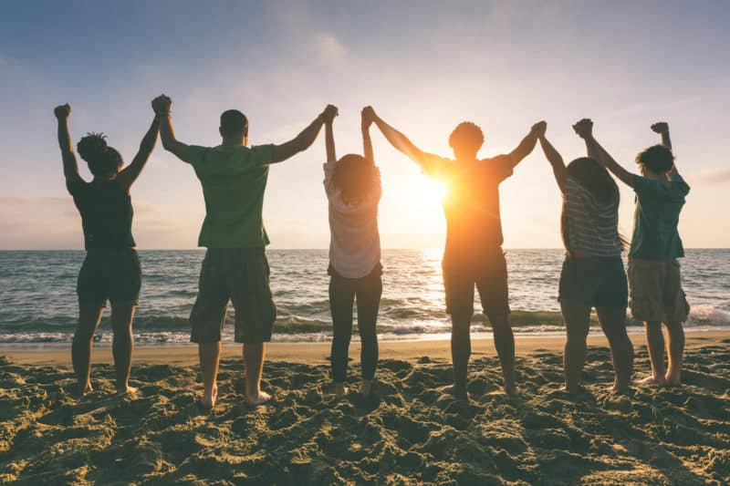 group of friends on beach hands joined in the air in rejoicing together
