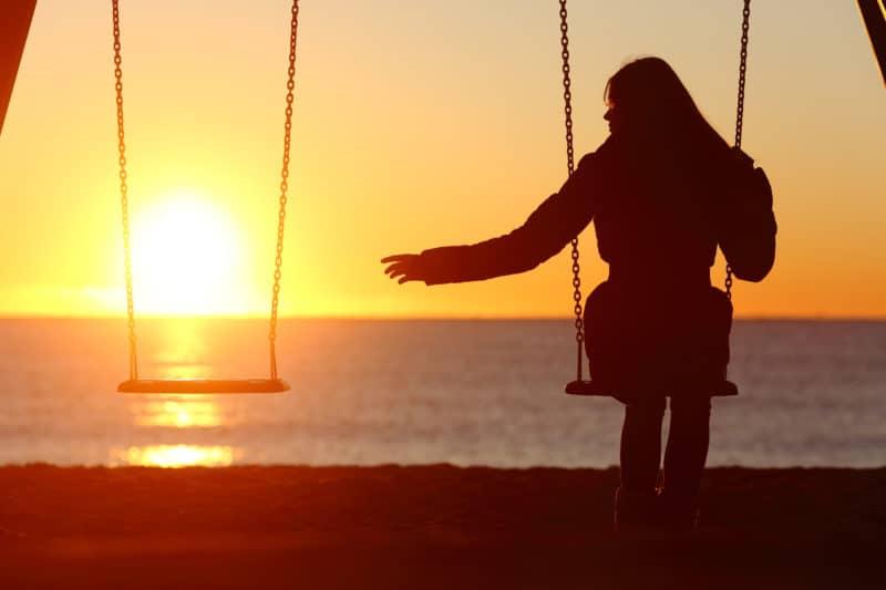 woman on swing reaching empty swing beside her | blog post on fighting comparison