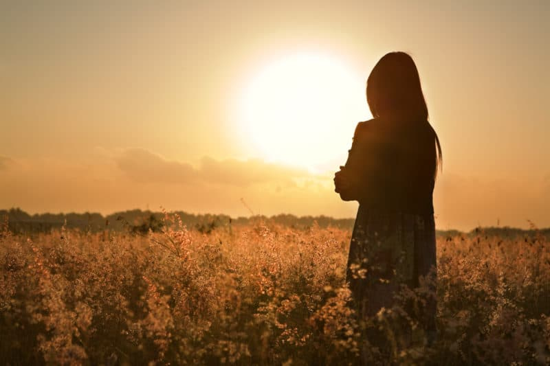 silhouette of woman wistfully overlooking a field | blog post on fighting comparison