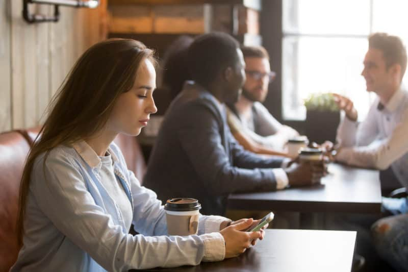 Woman sitting alone on her cell phone in a coffee shop | Article on 3 Ways Christian Community Builds Our Faith