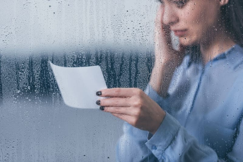 woman in front of rainy window crying as she reads a note | Finding faith in uncertainty and loss