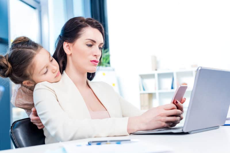 working mom on her phone while her young daughter looks patiently over her shoulder | An article on Grace & Truth to Help You Overcome Mom Guilt