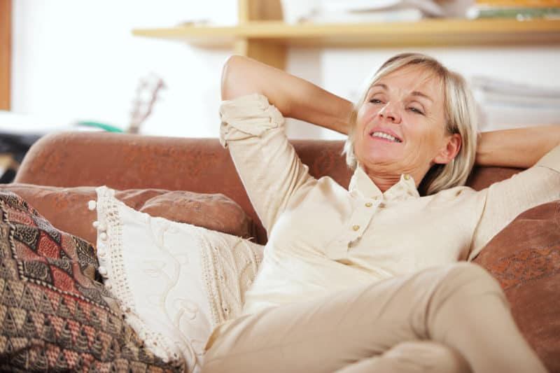 happy woman relaxing on couch | article titled: The Adjacent Possible: Applying Spiritual Disciplines to Your Life