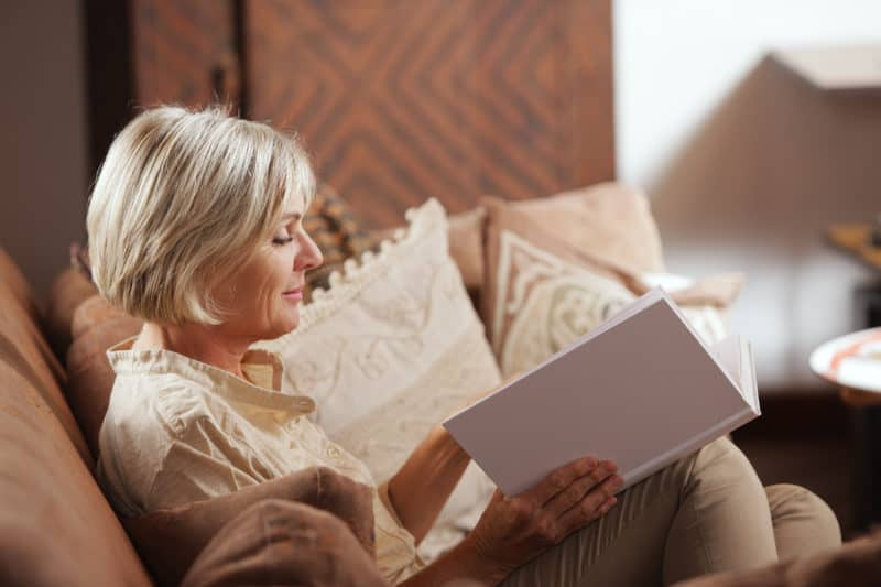 woman curled up on couch reading a book   article titled: The Adjacent Possible: Applying Spiritual Disciplines to Your Life