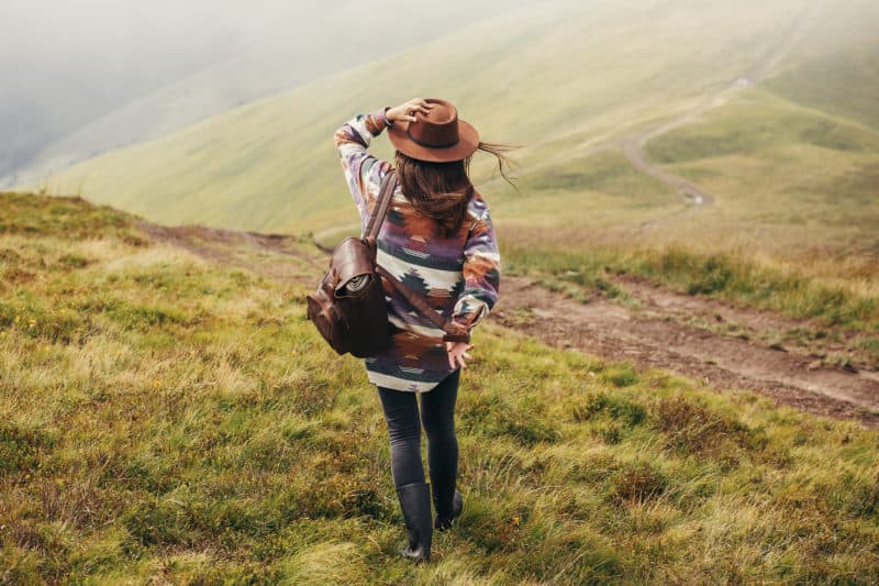 woman hiking through hills with backpack | Article on Broken Expectations: How to Trust God When Life Takes an Unexpected Detour