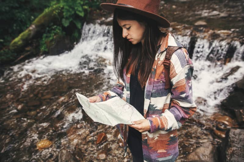 woman hiking near creek stopping to check her map | Article on Broken Expectations: How to Trust God When Life Takes an Unexpected Detour