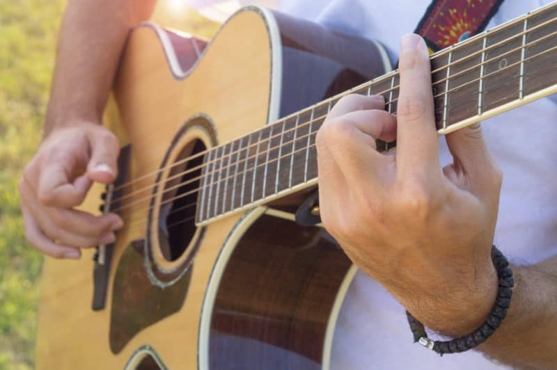 Man's hands and fingers playing acoustic guitar in the field | How to Praise & Pray Like David, A Free 6-Week Bible Study