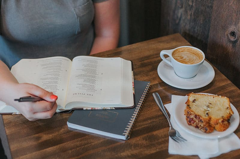 close-up of a woman having coffee with a pen in her hand as she studies the book of Psalms| Join us for our six-week summer study entitled: Pray Like David - A Study of David's Life & Psalms