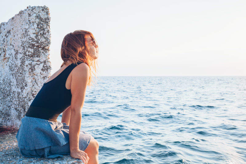 red-haired woman sitting on pier reflecting on her life and praying | article about 5 Steps to Trust God {When You Don't Feel Like It}