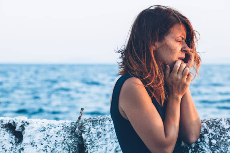 red-haired woman at the ocean pier feeling sad and lost | article about 5 Steps to Trust God {When You Don't Feel Like It}