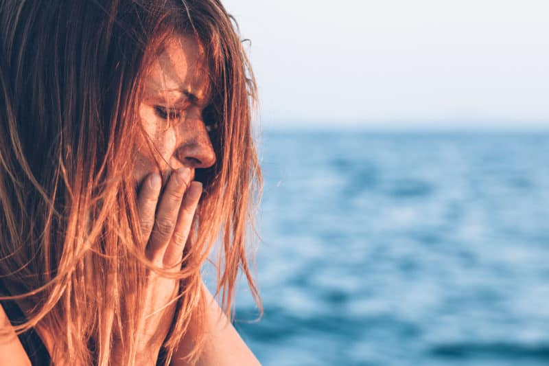 red-haired woman at the ocean with hands over her mouth feeling overwhelmed | article about 5 Steps to Trust God {When You Don't Feel Like It}