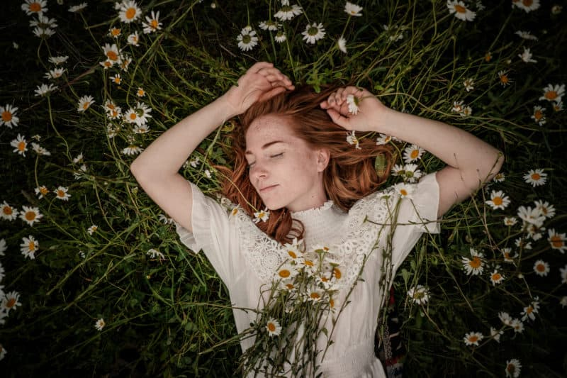 woman resting in a field of daisies | article on 3 Ways to Experience God's Rest