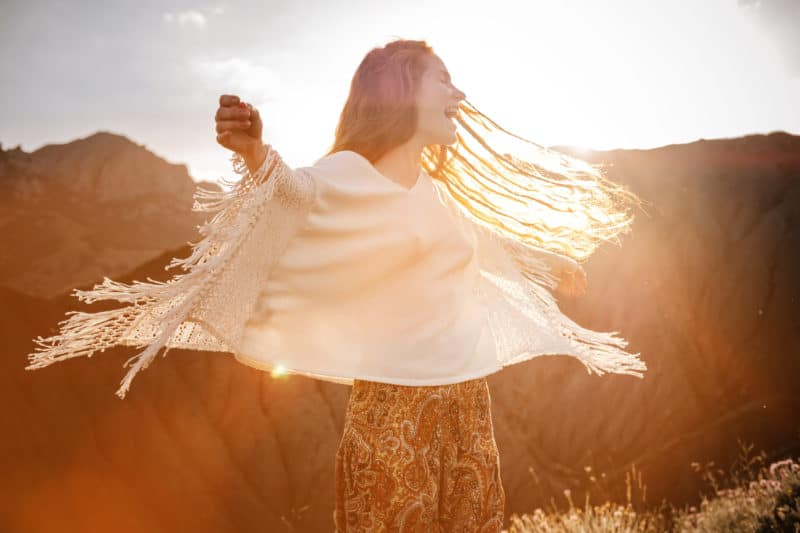 woman laughing in a field | article on 3 Ways to Experience God's Rest